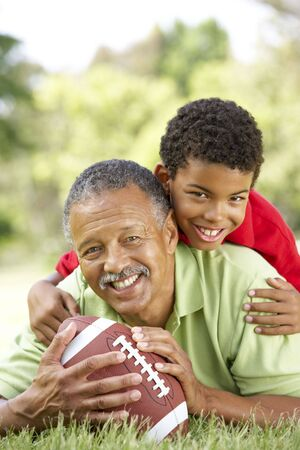 grandfather and grandson: Grandfather With Grandson In Park With American Football Stock Photo