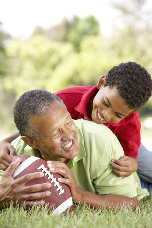 Grandfather With Grandson In Park With American Football photo