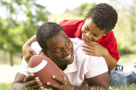 bola ocho: El padre y el hijo en el parque con el f�tbol americano