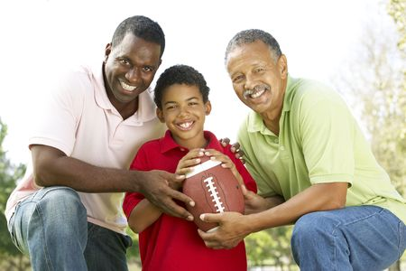 Grandfather With Son And Grandson In Park With American Football photo