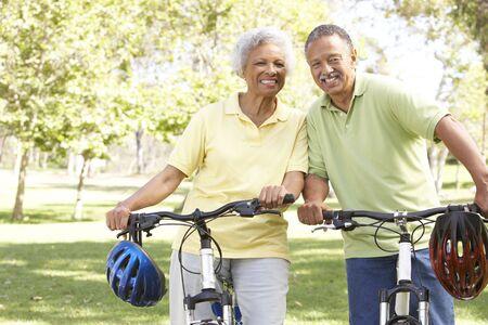 american seniors: Senior Couple Riding Bikes In Park