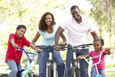 active family: Young Family Riding Bikes In Park