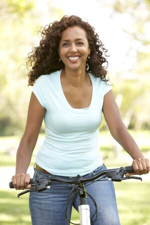 healthy path: Woman Riding Bike In Park Stock Photo