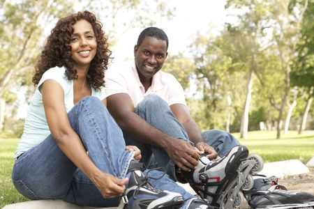 Couple Putting On In Line Skates In Park Stock Photo - 6456362