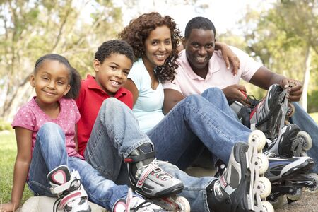 Family Putting On In Line Skates In Park photo
