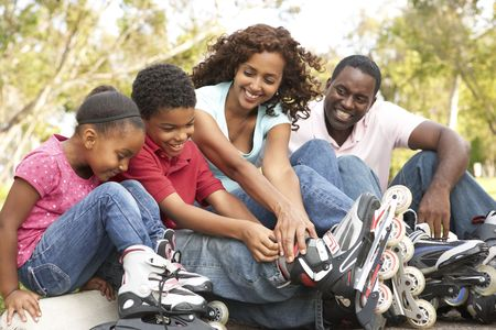 rollerblading: Family Putting On In Line Skates In Park