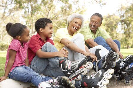 inline skating: Grandparent With Grandchildren Putting On In Line Skates In Park