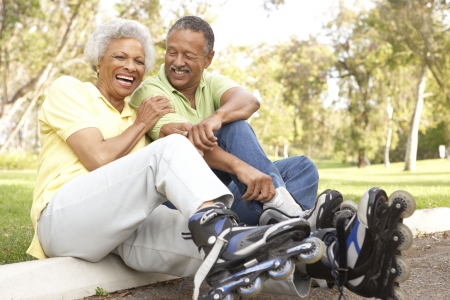 active woman: Senior Couple Putting On In Line Skates In Park Stock Photo
