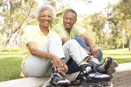 Senior Couple Putting On In Line Skates In Park Stock Photo