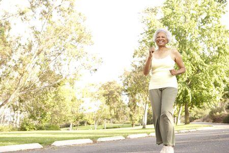 ジョグ: 年配の女性が公園でジョギング 写真素材