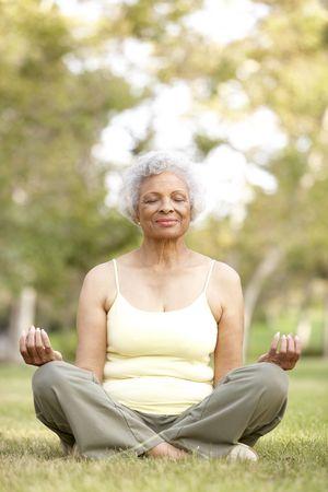 meditating: Senior Woman Doing Yoga In Park