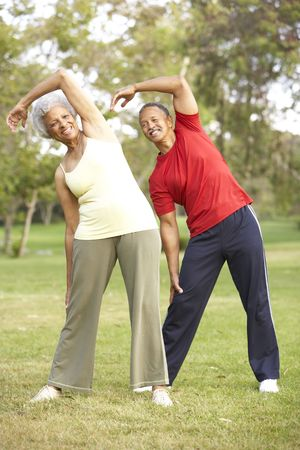 healthy seniors: Senior Couple Exercising In Park Stock Photo