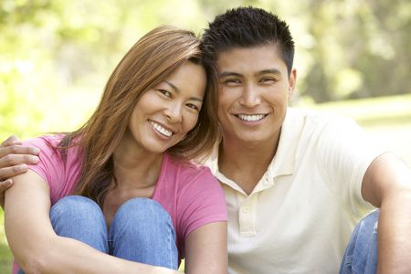 filipino people: Portrait Of Young Couple Sitting In Park