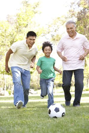 a generation: Grandfather With Son And Grandson Playing Football In Park Stock Photo