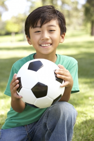 filipino people: Portrait Of Young Boy In Park With Football Stock Photo
