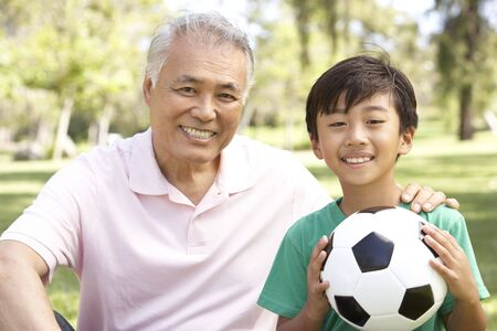 filipino people: Grandfather And grandson In Park With Football
