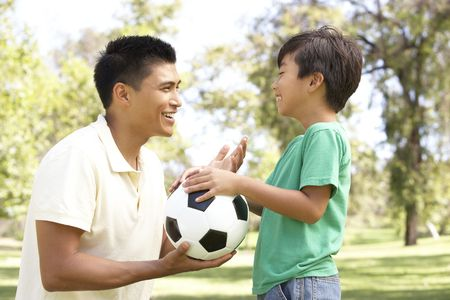 filipino people: Father And Son In Park With Football Stock Photo