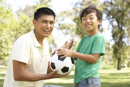 dad son: Father And Son In Park With Football Stock Photo