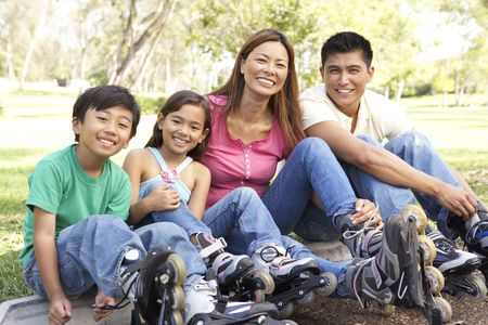 filipino people: Family Putting On In Line Skates In Park
