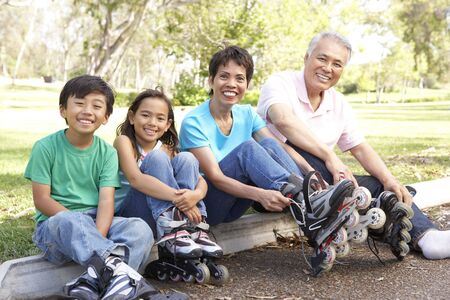rollerblading: Grandparents With Grandchildren Putting On In Line Skates In Park Stock Photo