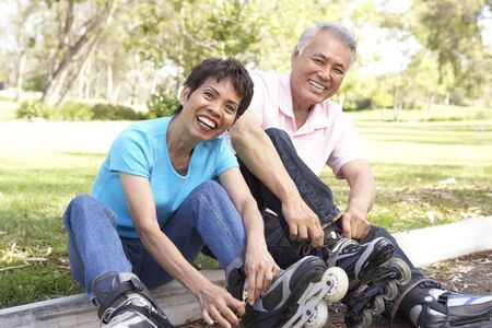 inline skating: Senior Couple Putting On In Line Skates In Park Stock Photo