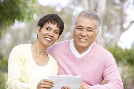 mujeres ancianas: Retrato de pareja Senior Looking At mapa
