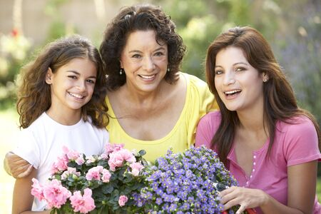grandmother grandchild: Senior Woman With Adult Daughter And Granddaughter Gardening Together