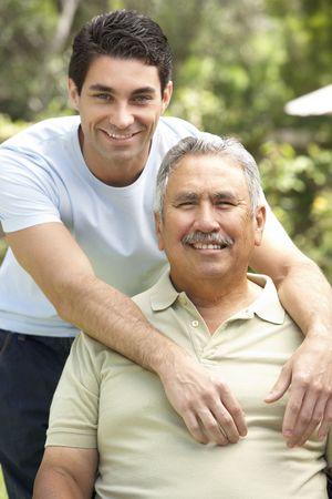 genegenheid: Senior Man met Adult zoon in tuin Stockfoto