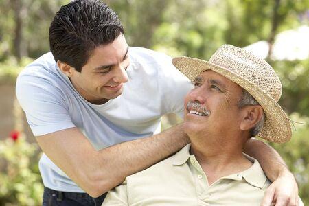 Senior Man With Adult Son In Garden photo