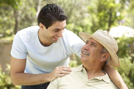 dad son: Senior Man With Adult Son In Garden Stock Photo