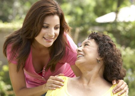 Senior Woman With Adult Daughter In Garden photo