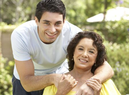 hispanic mother: Senior Woman With Adult Son In Garden Stock Photo