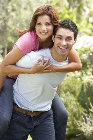 Young Man Giving Woman Piggyback Outdoors photo