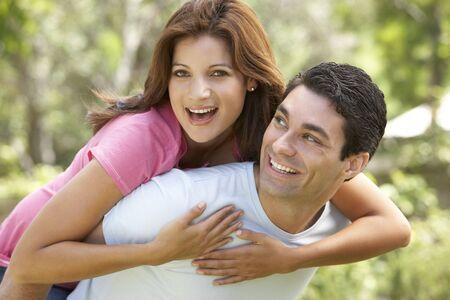 Young Man Giving Woman Piggyback Outdoors photo