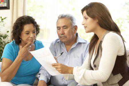 Senior paar met financieel adviseur thuis