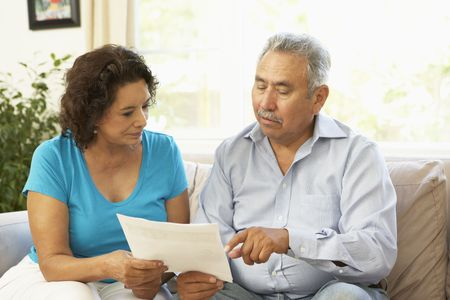 Senior Couple Studying Financial Document At Home photo