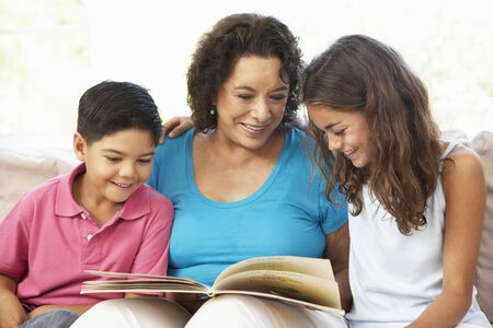 grandparent: Grandmother Reading With Grandchildren At Home Together