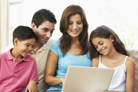 Family Sitting On Sofa At Home With Laptop Stock Photo - 6456387