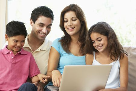 Family Sitting On Sofa At Home With Laptop photo