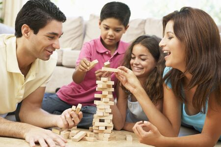 hispanic children: Family Playing Game Together At Home Stock Photo