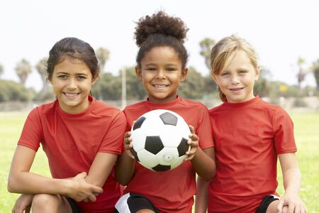 7 year old girl: Young Girls In Football Team Stock Photo