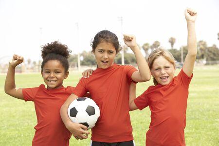niño y niña: Jóvenes Boys And Girls en fútbol Foto de archivo