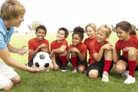 female soccer: Young Boys And Girls In Football Team  With Coach Stock Photo