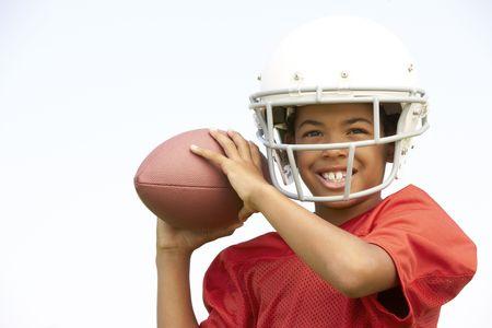 futbol infantil: Boy j�venes jugando f�tbol americano Foto de archivo