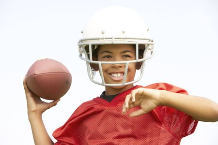 catching: Young Boy Playing American Football Stock Photo