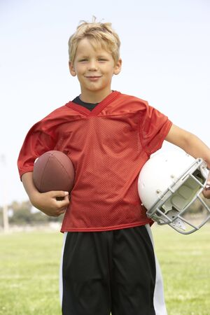 one little boy: Young Boy Playing American Football Stock Photo