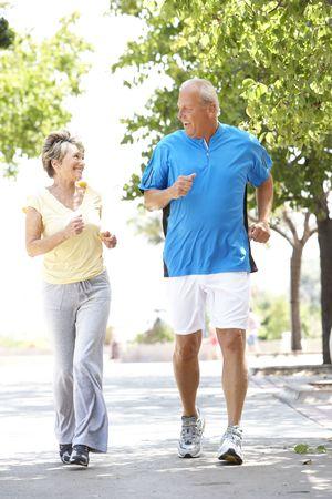 active couple: Senior Couple Jogging In Park Stock Photo