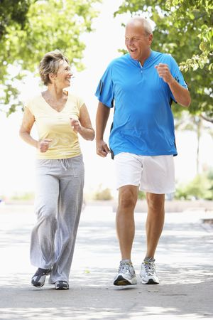 older men: Senior Couple Jogging In Park Stock Photo