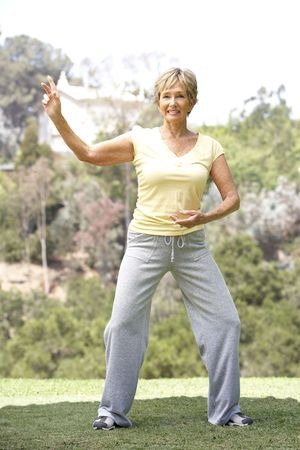 tai chi: Senior Woman Exercising In Park