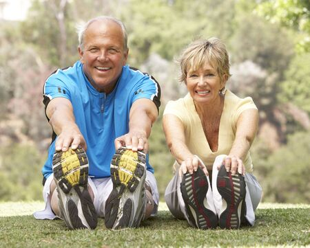 elderly couples: Senior Couple Exercising In Park Stock Photo